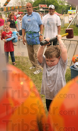"Tribune-Star/Joseph C. Garza<br /> After his brother, Skyler Tubb, left, 9, won his plastic blow up hammer, Ethan Tubb, 5, tried his hand at the ""High Striker"" Sunday at the Fairbanks Park Music and Arts Festival."