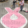 Tribune-Star/Joseph C. Garza<br /> First coat done: Ian Johnson and Gary Buck finish up the first coat of pink paint on the pink ribbon in the intersection of Wabash Avenue and Sixth Street Sunday.