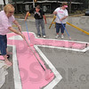 Painting awareness: Phylis Fouts of the Wabash Valley Breast Cancer Survivor Organization paints the pink ribbon in the center of the intersection of Wabash Avenue and Sixth Street Sunday with fellow volunteer painters, Ian Johnson and Nancy Buck.