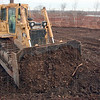 Improvements: Gary Henderson of Feutz Construction works last December tolevel fill material at the site of what will be the visitors center at the wetlands just east of West Terre Haute.