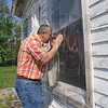 Tribune-Star/Joseph C. Garza<br /> Renovation plans: William Milner looks through one of the windows Tuesday of the county's only remaining octagon house near the corner of Chamberlain Street and Indiana 42. Milner is hoping to restore the home built in the 1850s.