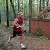 Feline feast: Tribune-Star reporter Brian Boyce runs past a caged tiger during Saturday's 5K race through the rescue center near Centerpoint.