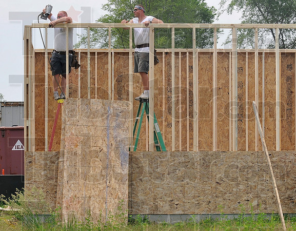 Tribune-Star/Joseph C. Garza<br /> A higher frame of mind: Terre Haute Fire Fighters Local 758 members Jim Likens and Jeff Monroe work on the frame of a Habitat for Humanity garage Saturday on south 15th Street.