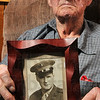 "Tribune-Star/Joseph C. Garza<br /> Commissioned: Brazil resident and World War II veteran, Melvin ""Jack"" Love displays a photo of himself after he was commissioned as an officer in the Marine Corps in Nov. 1945."
