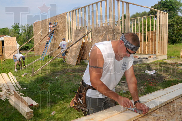Tribune-Star/Joseph C. Garza<br /> Wood work for a good cause: Terre Haute Fire Fighters Local 758 member Jeff Monroe marks sections of wood for the Habitat for Humanity garage on south 15th Street Saturday.