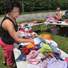 Tribune-Star/Joseph C. Garza<br /> Highway deals: Allison Pope sorts through the children's clothing she has for sale at her stand in Seelyville during the Historic National Road Yard Sale Saturday off of US 40.