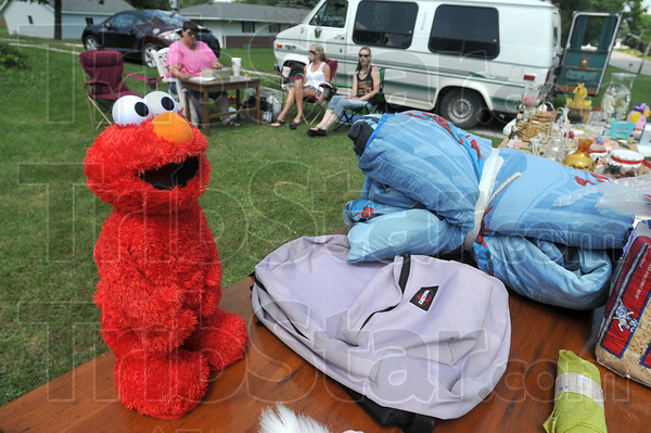 Tribune-Star/Joseph C. Garza<br /> Cuddly for sale: An Elmo doll sits for sale along US 40 in Brazil at Becky Hayes' yard sale Saturday during the Historic National Road Yard Sale. Sitting with Hayes are Brenda Thompson and Amber Schlatter.