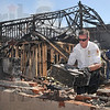 Tribune-Star/Joseph C. Garza<br /> Salvaging what they can: Terre Haute Fire Department Chief Jeff Fisher places a computer tower on the charred remains of a wall at Terry Modesitt's law office off of Ohio Street Wednesday.