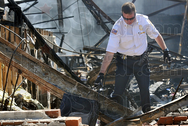 Tribune-Star/Joseph C. Garza<br /> Salvaging what they can: Terre Haute Fire Department Chief Jeff Fisher carries a computer tower out of the charred remains of Terry Modesitt's law office off of Ohio Street Wednesday.