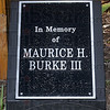 """Tribune-Star/Joseph C. Garza<br /> In memory: Plaques honoring the memory of John """"Jack"""" Roetker and Maurice H. Burke III are nestled among flowers and a flagpole in a large planter box dressing up the Vigo County Health Department's Vector Control Division on 7th Avenue near 13th Street."""