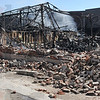 Tribune-Star/Joseph C. Garza<br /> So much lost: Sondra Rogers, the mother of Prosecutor Terry Modesitt, takes a photo of the smoldering remains of his law office Wednesday at the scene off of Ohio Street.