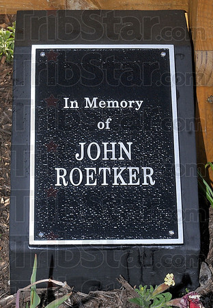 "Tribune-Star/Joseph C. Garza<br /> In memory: Plaques honoring the memory of John ""Jack"" Roetker and Maurice H. Burke III are nestled among flowers and a flagpole in a large planter box dressing up the Vigo County Health Department's Vector Control Division on 7th Avenue near 13th Street."