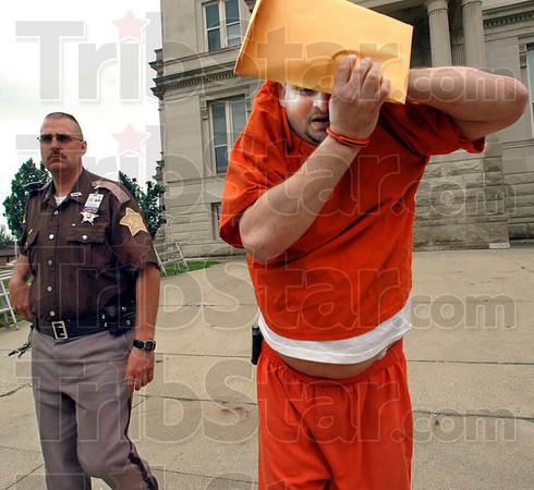Fifty years: Robert G. Martin attempts to hide his face as he's being returned to the Vigo Co. Jail after being sentenced to 50 years in prison for the dismemberment killing of Nikolle Steelman Wednesday morning.