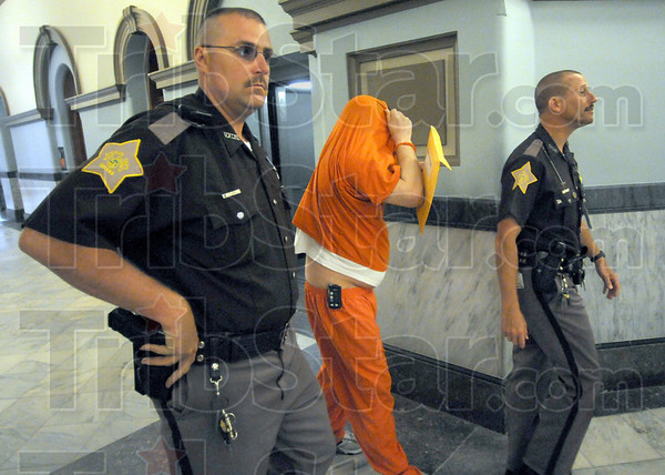 Arrival: Robert G. Martin attempts to cover his face as he walks to the Vigo Co. Courtroom of Judge Michael Eldred to be sentenced in the dismemberment killing of Nikolle Steelman Wednesday morning.
