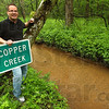 New name: Chris Nasser stands on the bank of Copper Creek in eastern Vigo county. The sign is scheduled to be placed nearby on Old Ft. Harrison Road this Friday.