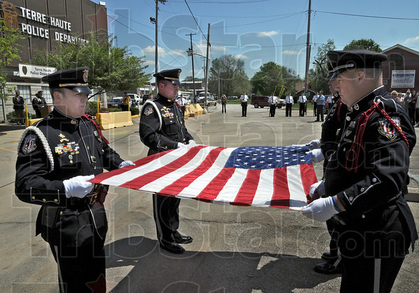 Flag folding: Members of the Terre Haute Police Department Honor Guard prepare to fold the flag during a memorial service Monday afternoon at police headquarters.
