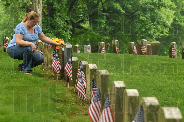 Tribune-Star/Joseph C. Garza<br /> Remembering dad: RoxeAnne Kesner kneels next to her father Robert Harris' grave stone during a visit to Highland Cemetery Monday. Harris was a U.S. Army Sgt. during World War II and died in 2007.