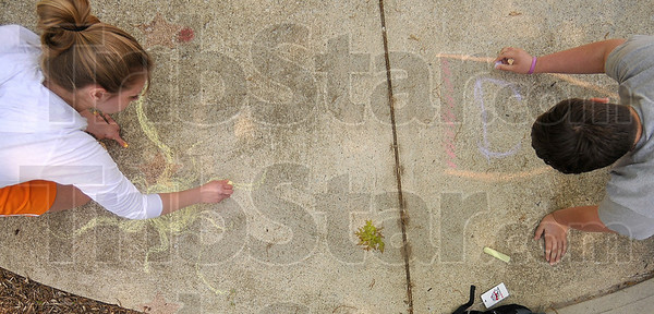 Tribune-Star/Joseph C. Garza<br /> Sun and fun: Rose-Hulman sophomore Rachel Holscher of Vincennes and sophomore Scott Gallmeier of West Terre Haute draw on the sidewalk with chalk made available at the engineering school Tuesday.