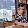 Tribune-Star/Joseph C. Garza<br /> Reeling from the economic tail spin: Revolutions co-owner Dennis Ross relaxes outside of the 421 Wabash Avenue shop between customers Tuesday afternoon. Like the sign in the window says, the store is closing.