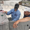 "Tribune-Star/Joseph C. Garza<br /> Cool in summer, warm in winter: Carrier employee Mike Reed and B&S Plumbing employee Mike Dalton look over the air conditioning system on top of the new Citizens National Bank at 315 E. Davis Drive Tuesday. The white roof is part of the new bank's ""green"" construction which will help it stay cool in the summer and warm in the winter."