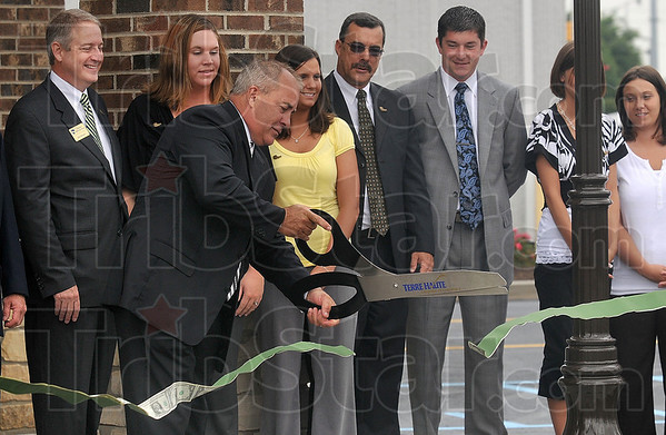 "Tribune-Star/Joseph C. Garza<br /> Open for business: Citizens National Bank Chairman of the Board George Rogers cuts a green ribbon during the grand opening ceremony for the company's new ""green"" bank Tuesday at 315 E. Davis Drive."