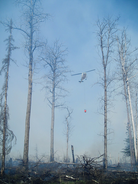 Forestry's helicopter maintained constant support overhead with bucket drops on hotspots.