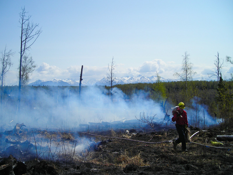 Tim Gonyea runs hoses along the fireline in an effort to get a secured perimeter.