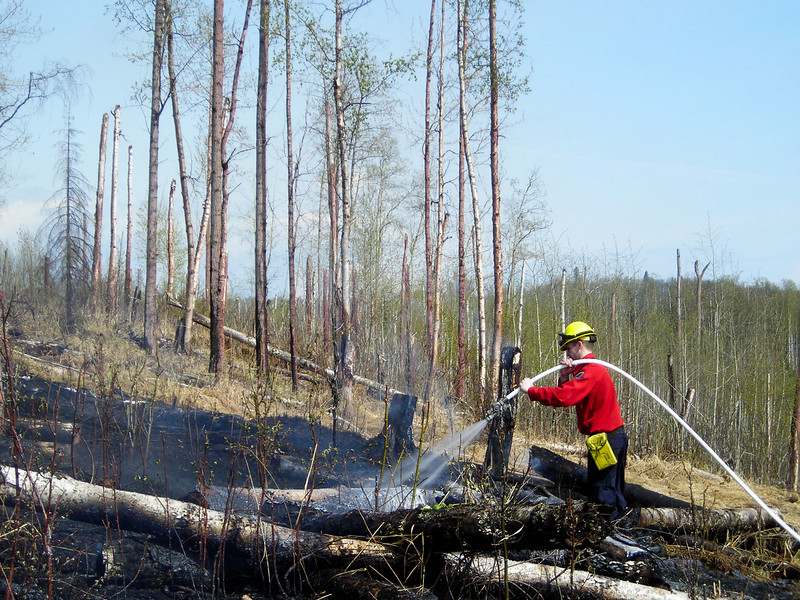 """Tim Gonyea patrols the south flank of the fire, securing the perimeter before moving into the """"black"""" to extinguish hotspots."""