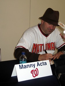 Nationals manager Manny Acta signs autographs