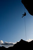 The mountains look on as Kelsey Gray takes to the open air on the long rappel after completing our route.