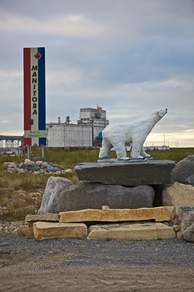 A polar bear statue in front of the Churchill grain elevators, the most prominent building in the small town (average population throughout the year of about 1000). The grain elevators are used to load grain, brought north on the railway, on to ships to be carried (with other cargo) to Montreal and Toronto, the eastern United States, and to Liverpool for distribution across the continent. Although it looks so far north and east on the map (because it is so far north and east), Churchill is the same distance from Liverpool as it is from New York: the Great Circle principles work in its favour in this regard.