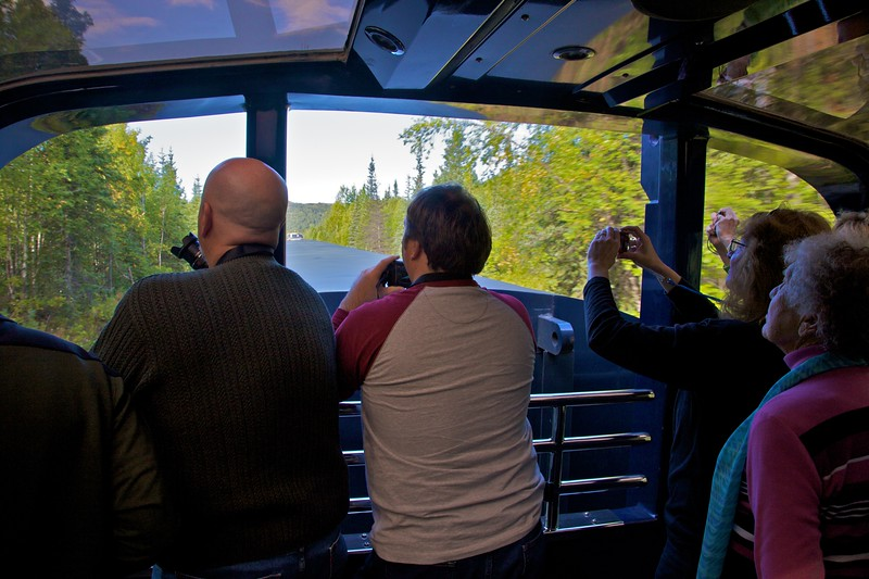 Tourists on my train in the (covered) open platform at the back of the upper level of our carriage, taking advantage of the (somewhat extraordinary) clear weather allowing us to see the peak of Mt McKinley from the train.