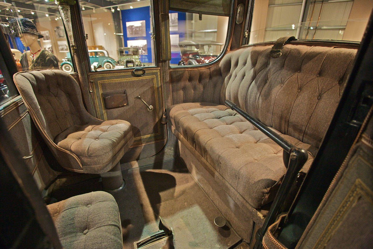 The inside of a 1912 Rauch & Long Electric Brougham car, which is described as 'a drawing-room on wheels'. The driver sits on the bench at the right of the photo—the back of the car—and two of his passengers can sit facing him at the front of the car. (In the Fountainhead Antique Car and Auto Museum, Fairbanks.)