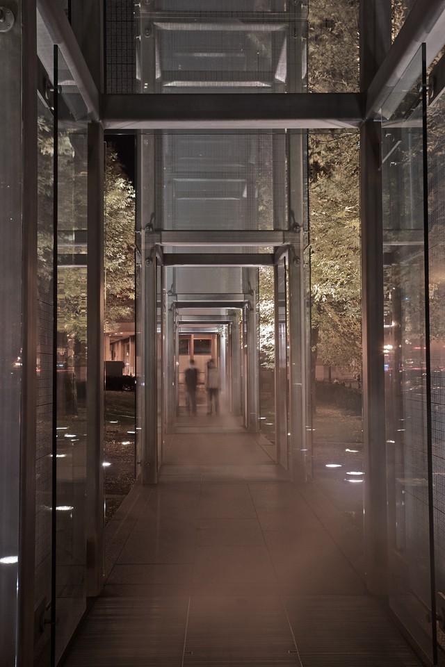Figures walk through the pillars of steam at the New England Holocaust Memorial.
