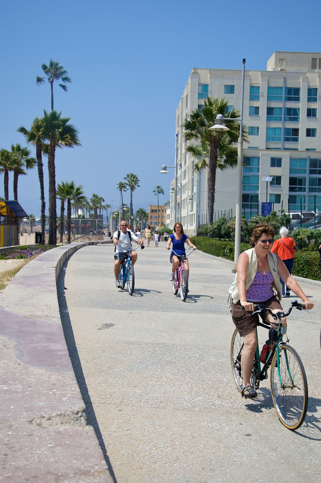 Bicyclists passing along the top of Santa Monica beach.