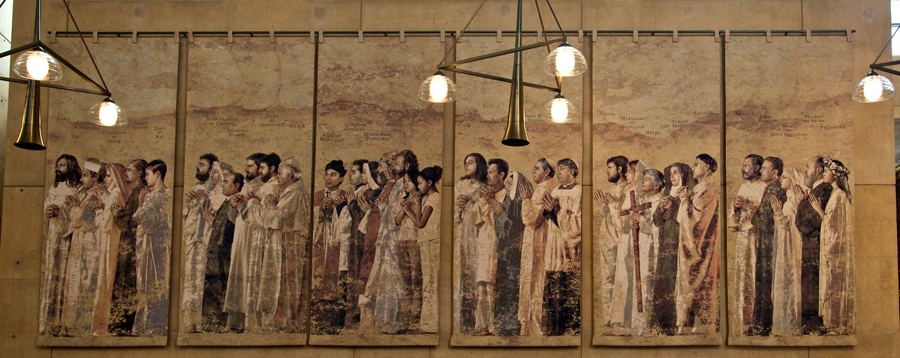 Saints in the cathedral of Our Lady of the Angels, Los Angeles: Andrew Dung Lac, Aloysius Gonzaga, Marie-Rose Durocher, Stephen of Hungary, Matthew, John, Lorenzo Ro… [unreadable], Justin, Margaret of Scotland, Helen, Louise de Marillac, Emydius, Philip, John Bosco, Mary of Jesus Crucified, Francis de Sales, Philomena. [Brownie points to those who can identify those saints whose names are blocked in this photo.]