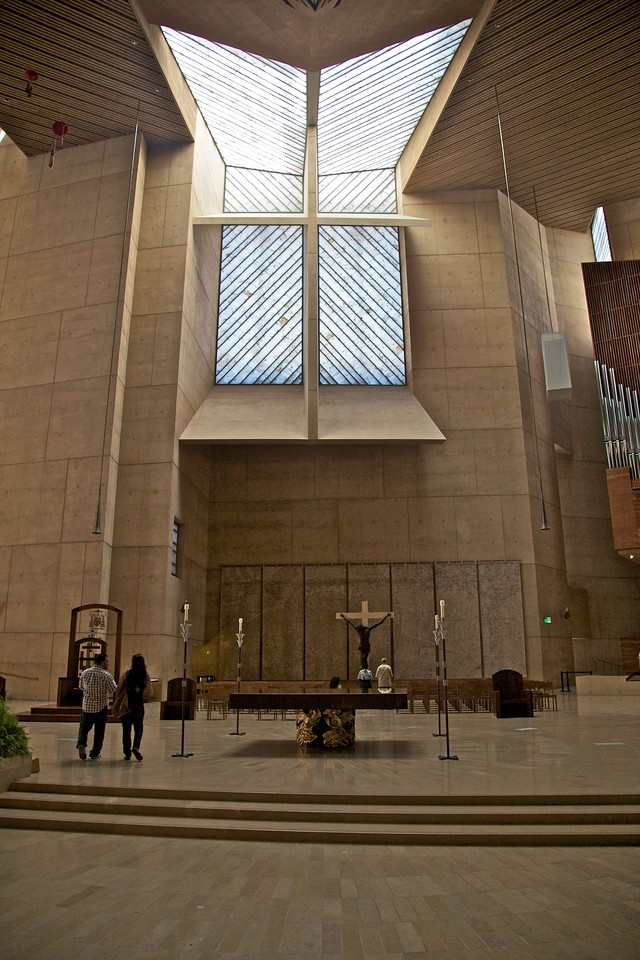 The sanctuary of the cathedral of Our Lady of the Angels in Los Angeles. It took me a while at Mass before I realized that the alabaster window above the sanctuary was divided up by a cross shape. The horizontal bar of the cross slopes downward from back to front, thus maximizing the amount of light coming in from the top two quadrants.