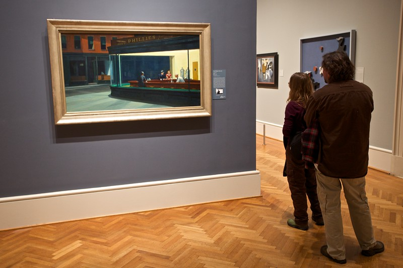 Gallery visitors at the Art Institute of Chicago with Edward Hopper's (1882–1967) 'Nighthawks' (1942). This painting has fascinated me for a while—it seems completely mundane at first but before long you find that it leaves you with more questions than it answers: who are these people? Why is the man on his own? And why is there no door to get from the milk bar to the outside world?! I don't mind admitting that my desire to see the painting in real life meant that I was sure to put Chicago on my itinerary at a very early stage of planning my North-American trip.  I really became aware of Edward Hopper when I read Alain de Botton's <cite>The Art of Travel</cite> (2002), especially chapter II, 'On travelling places'.  I'm definitely a fan of art galleries that allow visitors to take photographs. I find it very interesting to see and depict how other visitors interact with paintings and other pieces of art—if all you want to see is the artworks, you'd be better off getting a postcard, looking in a book, or finding a picture elsewhere on the Web. What we see here, though, is a common attitude of gallery-visitors: to the side, concentrating on the label more than on the painting itself. The label can sometimes act as a safety barrier, telling the visitor what to think rather than requiring him to form his own opinion about an artwork. I know that I certainly do this sometimes—on occasion I flit from label to label with barely a glance for the paintings!