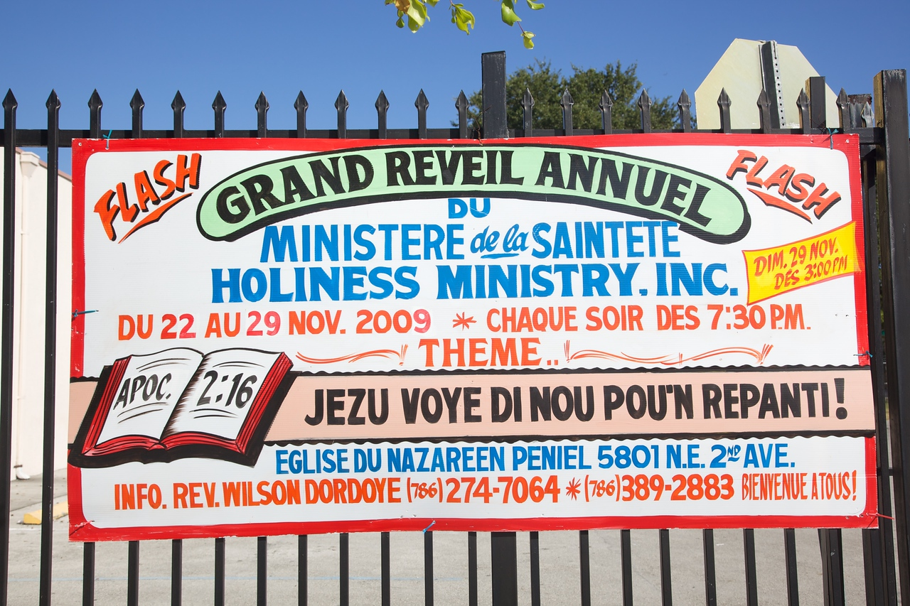 A hand-painted sign (on corrugated plastic) outside a Protestant church in the Little Haiti neighbourhood of Miami. Different parts of the notice are written in French, English, and Haitian Creole.