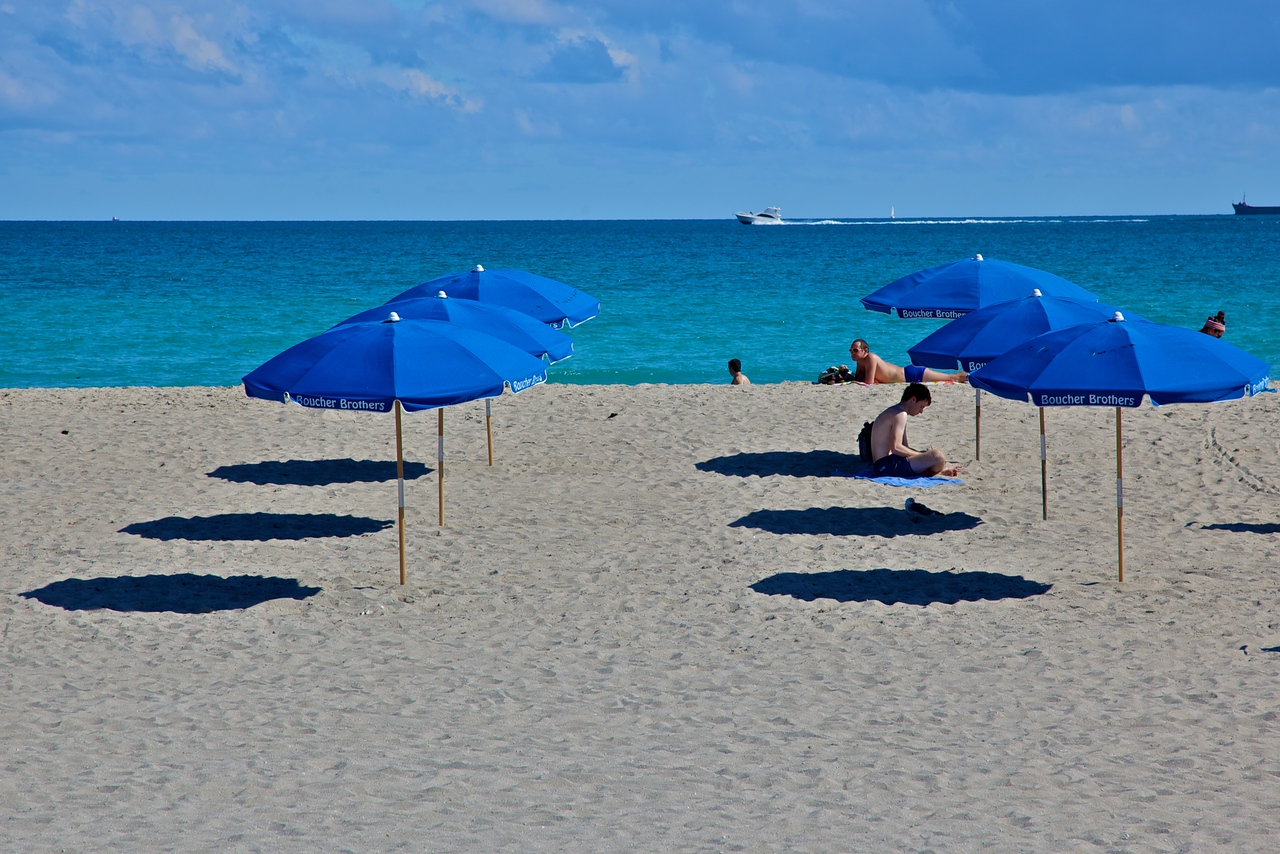 People on Miami Beach in November 2009. Miami Beach is a city separate from the city of Miami, on the barrier islands which separate Biscayne Bay from the Atlantic Ocean. This is the ocean side.