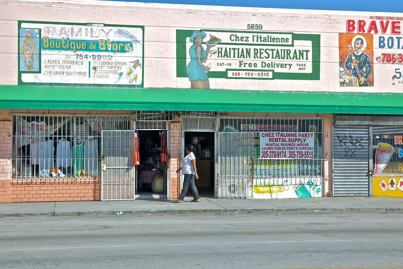 A woman walks past a restaurant in the Little Haiti neighbourhood of Miami.