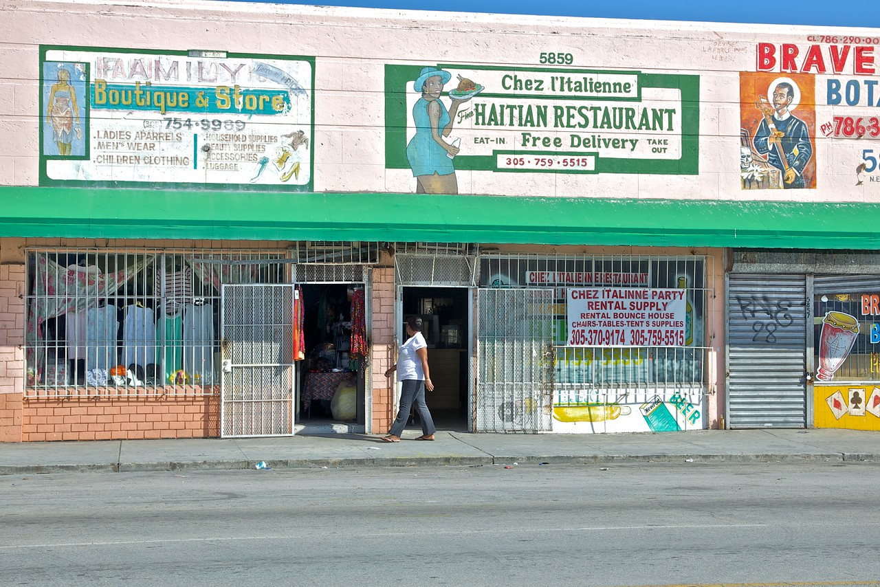 A woman walks past a restaurant in the Little Haiti neighbourhood of Miami.