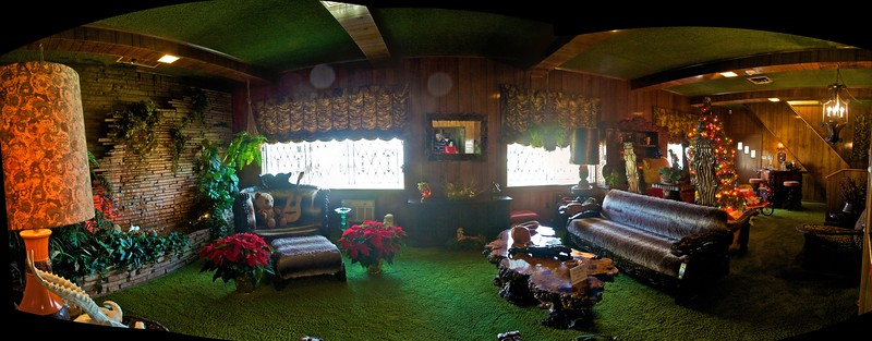 Four-frame stitched photo of the Jungle Room at the back of the Graceland Mansion. This room has to be seen to be believed. I know that when I'm putting green shag carpet in a room I put it on the ceiling as well as the floor. Also, check out the built-in exposed-brick water feature at the left-hand end of the frame. The photo (with difficult lighting) doesn't quite do justice to the wooden-animal arms on the leather sofa and armchair.