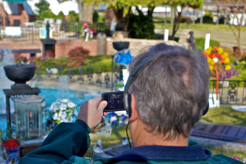 A man photographs Elvis'grave on his iPhone.