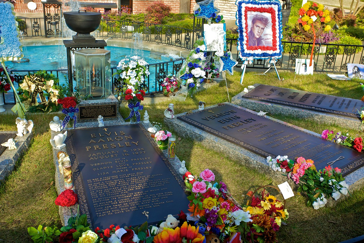 The grave stones of Elvis and his parents, surrounded by the flowers and other tributes imported and sent by the continuing phalanx of Elvis devotees.