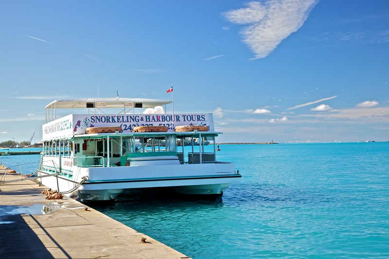 A tour boat moored along the shore in Nassau, waiting to take on passengers.