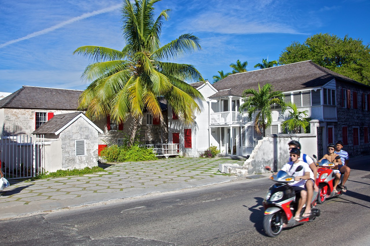 Tourists pass a house in Nassau on motorcycles. When choosing photos to publish, I was vacillating over this one and one of the house on its own with the top of the tree visible.