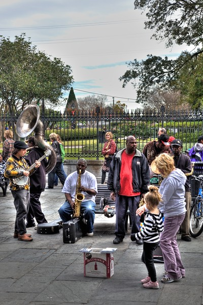 A mother and daughter pass by a band performing in Jackson Square.