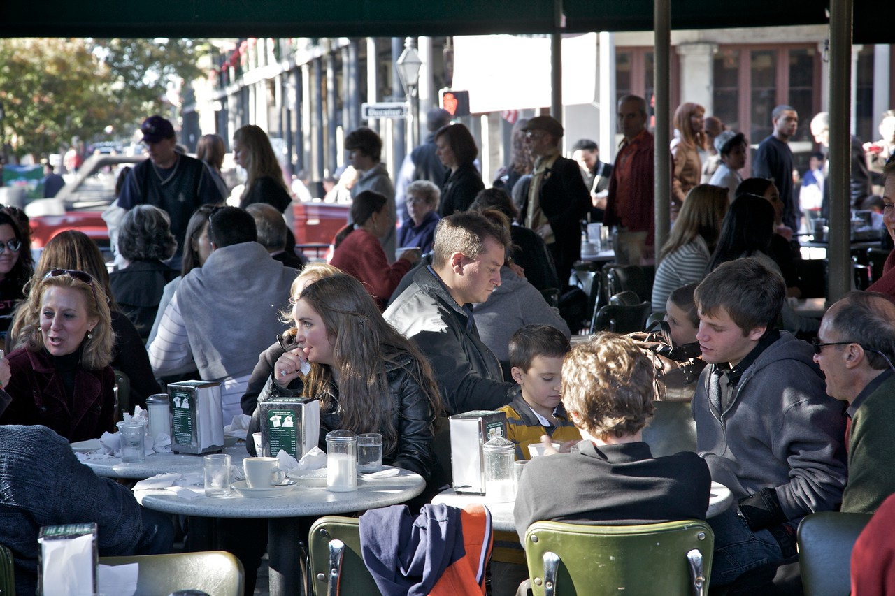 Families at the Café du Monde on Thanksgiving Day, 2009. In the background you can see people queuing for a table.