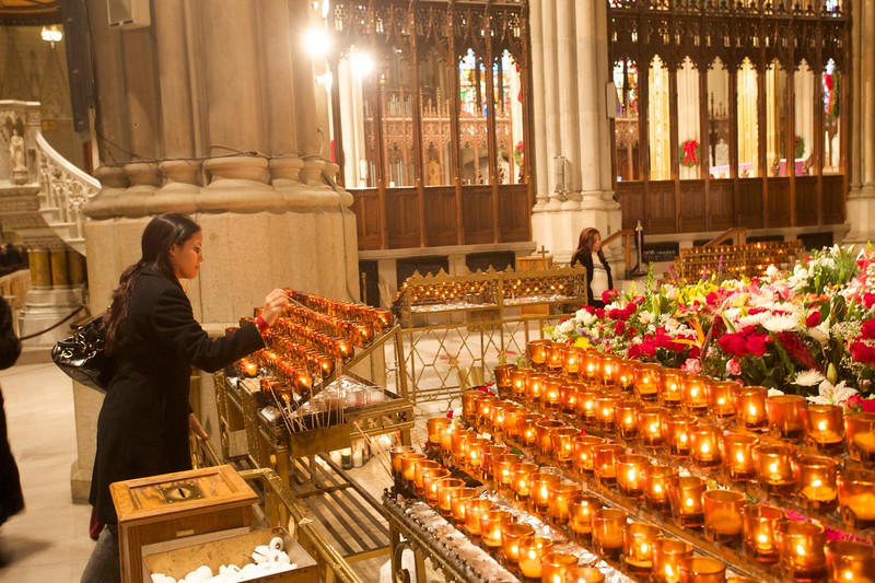 A woman lights a devotaional candle in front of the icon of Our Lady of Guadalupe on 14th December 2009. At Mass the previous day, the Archbishop of New York had thanked those who had sent flowers for the feast of Our Lady of Guadalupe on 12th December.